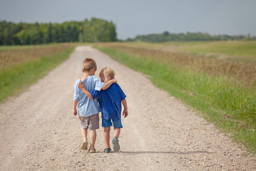 Two Caucasian Boys Walking Down A Country Road Stock Photo - Download Image Now