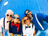 istock Two caucasian couples have fun and smile at the camera for a selfie. Behind them a blue striped wall. Concept of cheerfulness and positivity for two generations of family 1158760347
