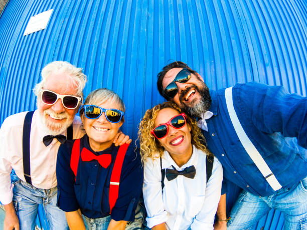 Two caucasian couples have fun and smile at the camera for a selfie. Behind them a blue striped wall. Concept of cheerfulness and positivity for two generations of family Two caucasian couples have fun and smile at the camera for a selfie. Behind them a blue striped wall. Concept of cheerfulness and positivity for two generations of family suspenders stock pictures, royalty-free photos & images