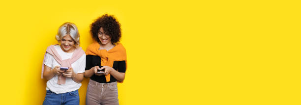 Two caucasian girl with curly hair chatting on their phones on a yellow wall with free space stock photo