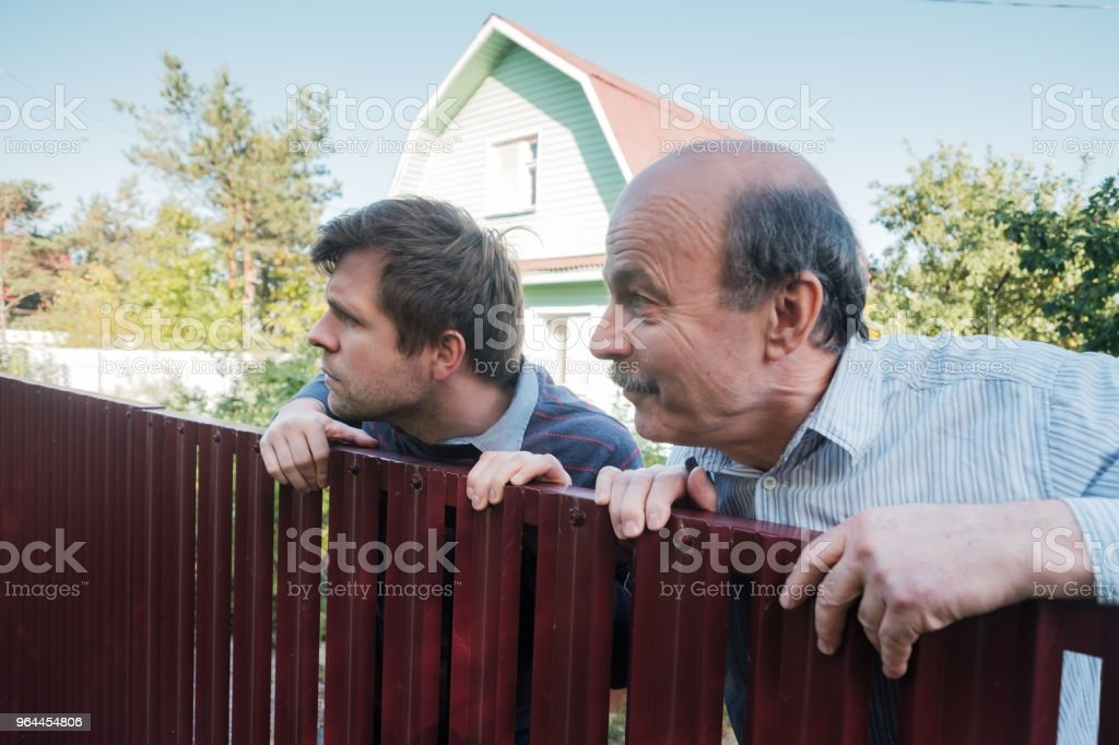 two caucasian men carefully watching over the fence. stock photo