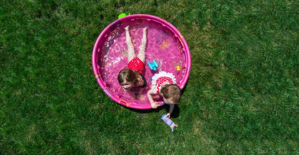 Zwei kaukasischen Kleinkind braun behaarte Mädchen spielt In einem rosa Hinterhof Kiddie Pool während A heißen Sommertag – Foto