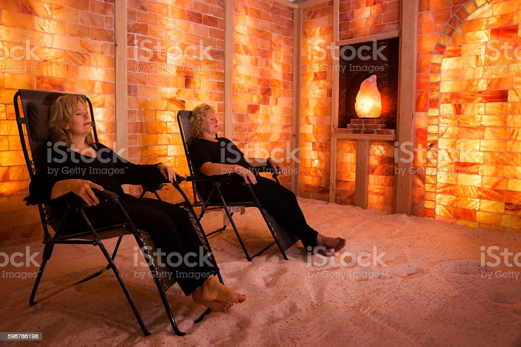 Two Caucasian women relax with salt lamps stock photo