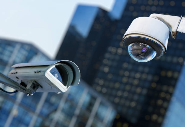 two cctv security camera in a city with blury business building on background - big brother imagens e fotografias de stock