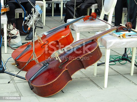 Two Cello Bow Instrument in orchestra on a stage