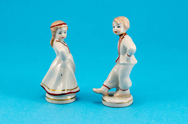 two ceramic toy decor dancers boy girl on blue - figurine stock photos and pictures