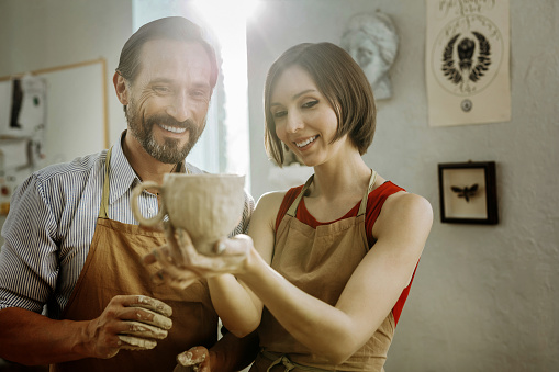 Two ceramists feeling relieved after making nice big cup