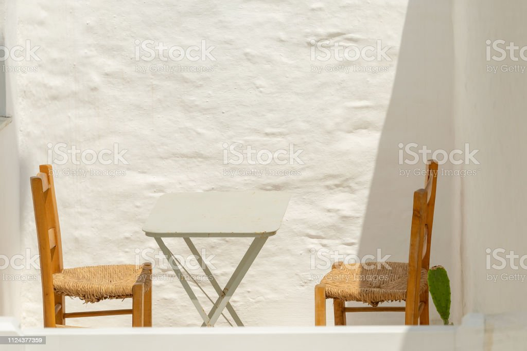 Two chairs and a table. Retro scenic at Andros island in Greece. stock photo