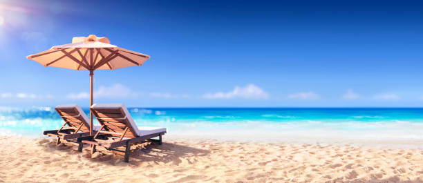 Two Chairs And Parasol With In The Golden Beach stock photo