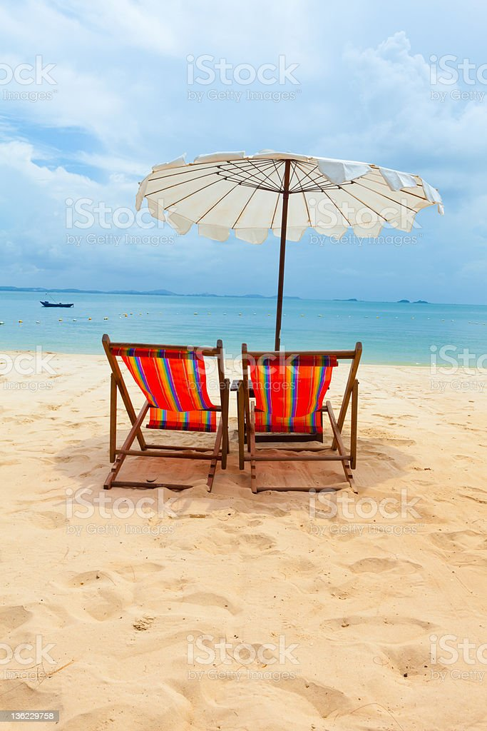 Two chairs in the sand under umbrella on beach royalty-free stock photo