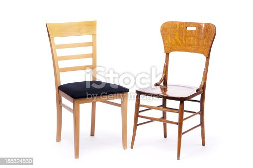 A contemporary, simple beech wooden side chair with a black cloth cushion sitting next to an old hardwood oak, country-style dining chair, angled as if the chairs are in an intimate conversation. Cut out and isolated on a white background.