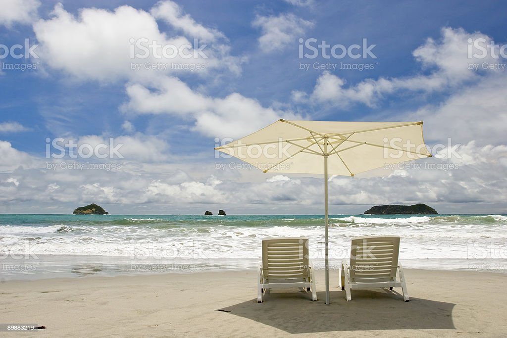 Two chairs sitting on the beach royalty-free stock photo