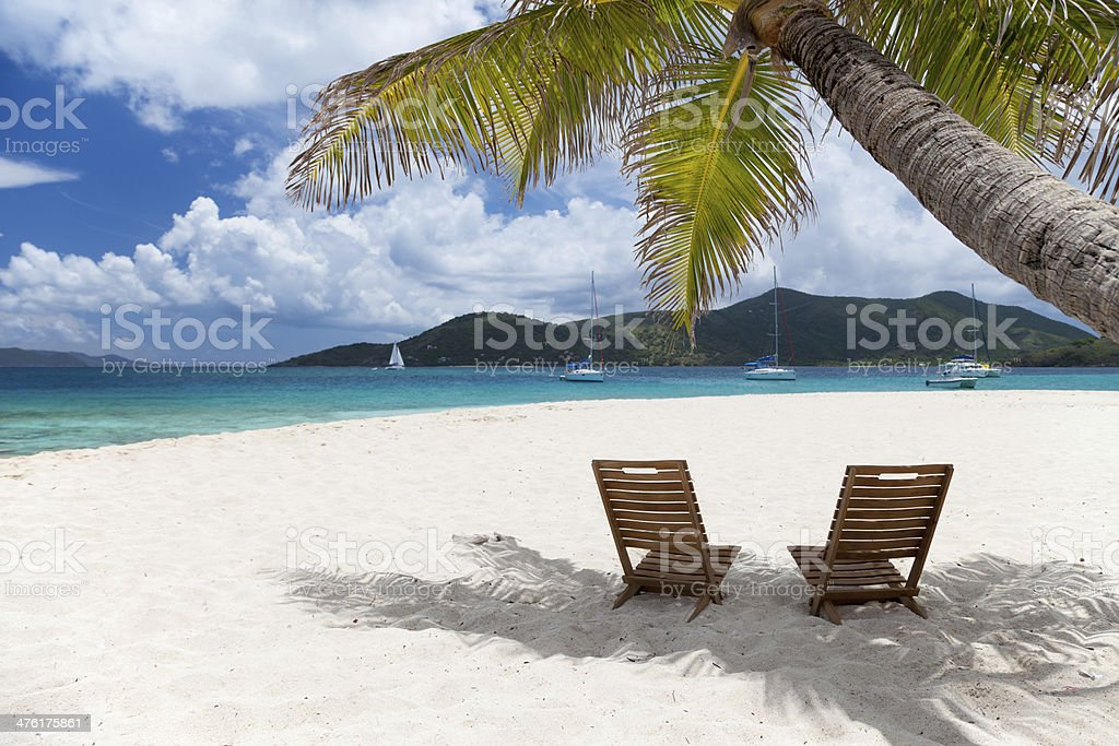 two chairs under a palm tree at the Caribbean beach stock photo