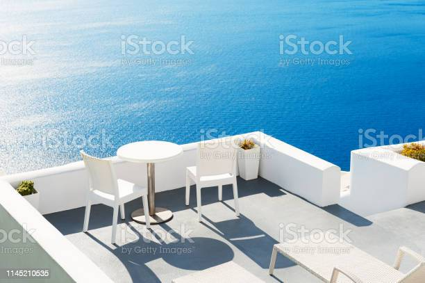 Two chairs with table on the terrace overlooking the sea santorini picture id1145210535?b=1&k=6&m=1145210535&s=612x612&h=apzhengfsc7gzd032jd2sg8axbo4iboglzb th kh1m=