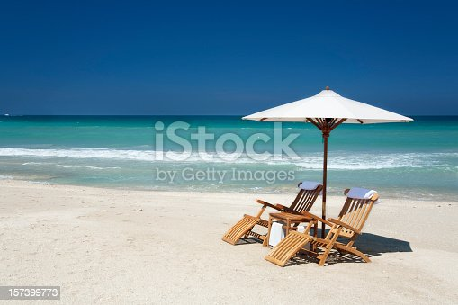 two teak chairs with white umbrella on a beach in Florida