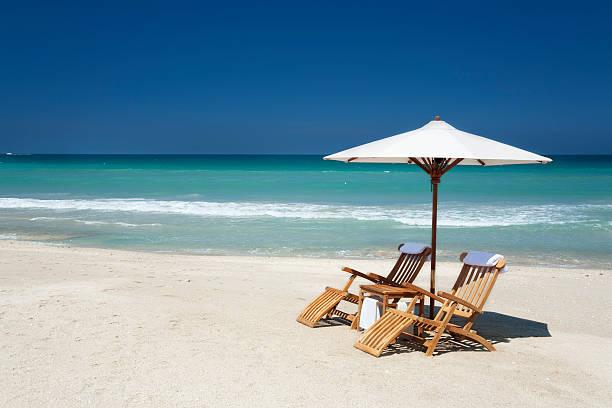 zwei stühle und sonnenschirm am strand in florida - sun chair stock-fotos und bilder