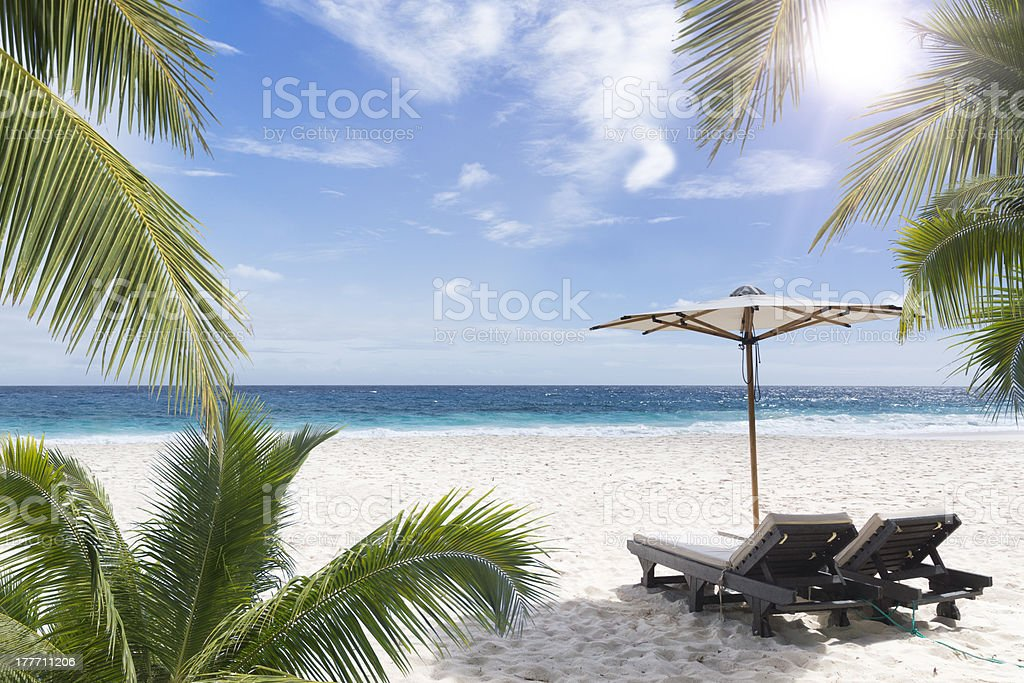 Two chairs with umbrella on a white sand Seychelles beach royalty-free stock photo