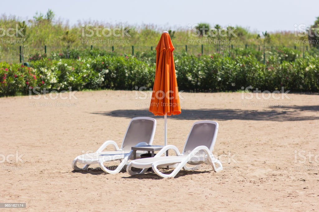 Two chaise lounges stand on the sand with a closed umbrella royalty-free stock photo