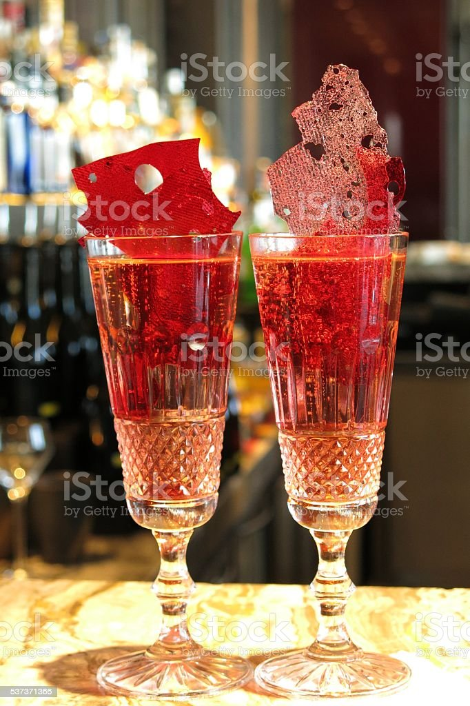 two champagne and raspberry cocktails on a bar stock photo