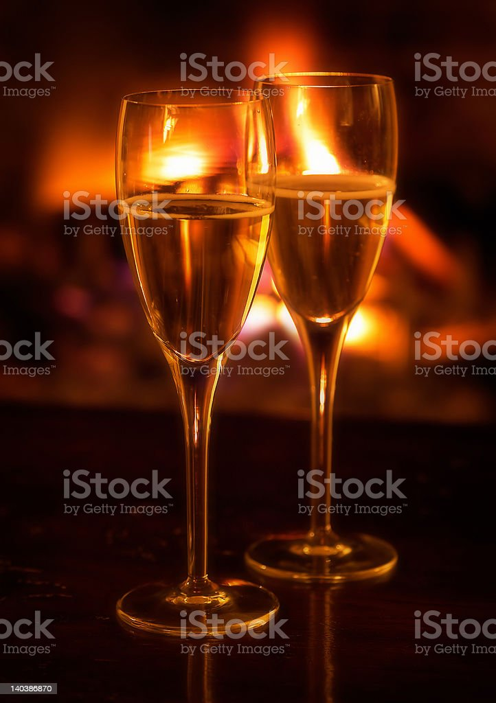 Two champagne flutes lit by log fire royalty-free stock photo