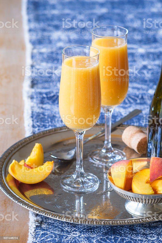 Two champagne flutes with Bellini coctail stock photo