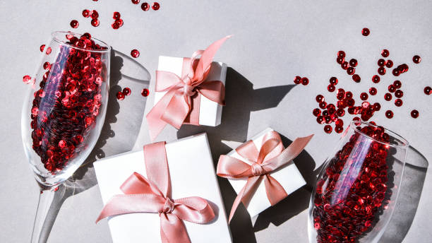 two champagne glasses and gift boxes isolated on an empty pink festive background, copy space, valentines day stock photo