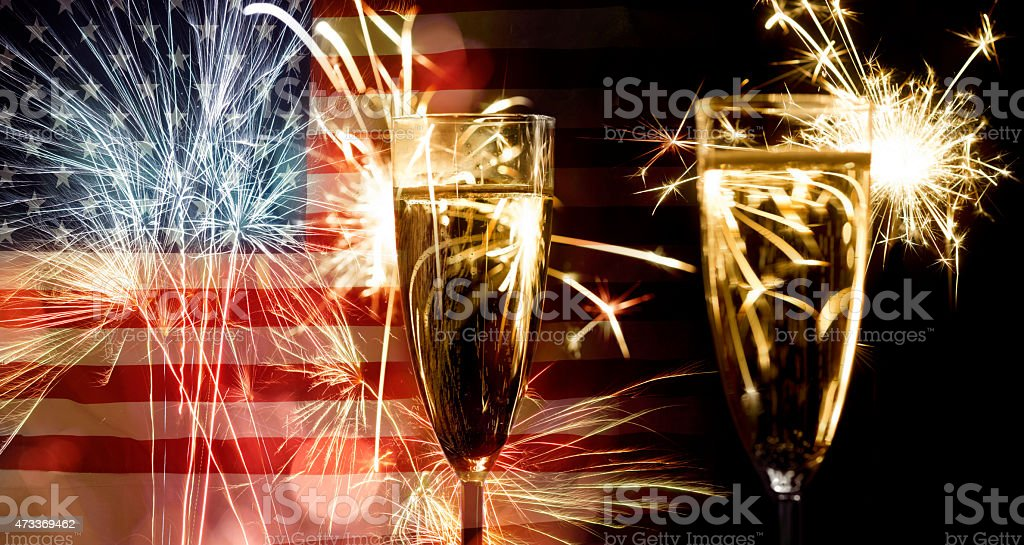 Two champagne glasses fireworks and an American flag stock photo
