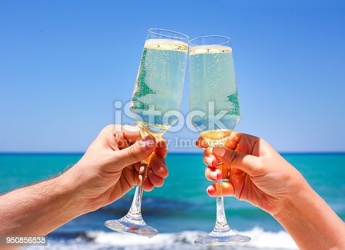 istock Two champagne glasses in man and woman hands 950856538