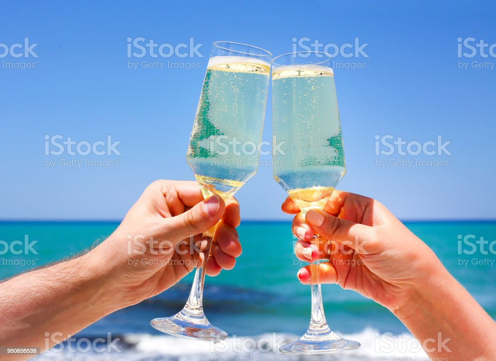 Two champagne glasses in man and woman hands stock photo
