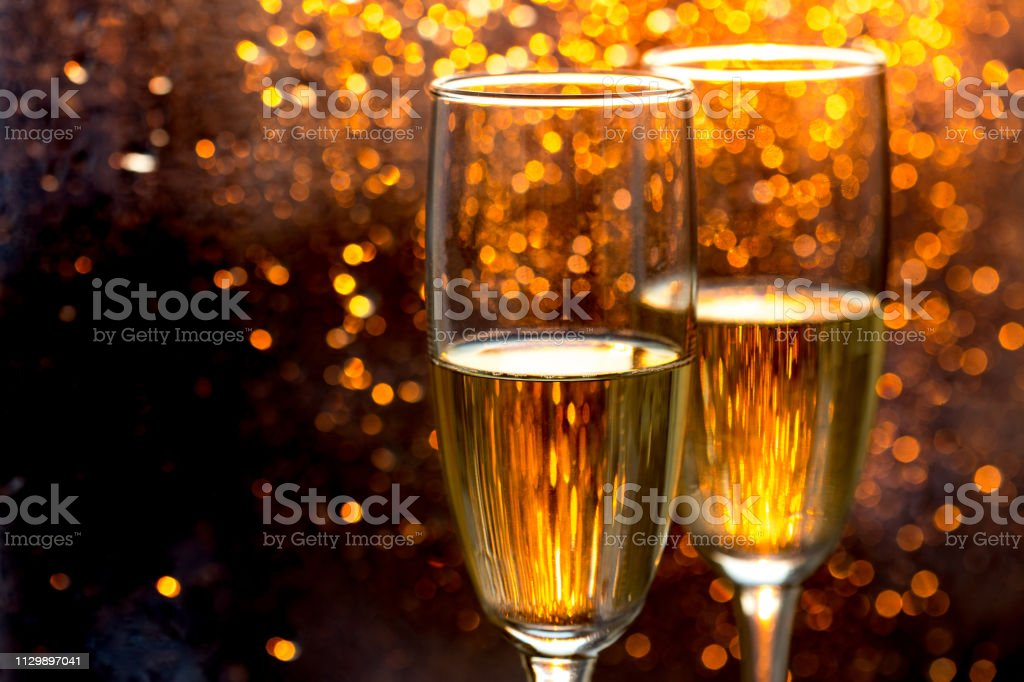 Two champagne glasses of toasting against dark gold bokeh background