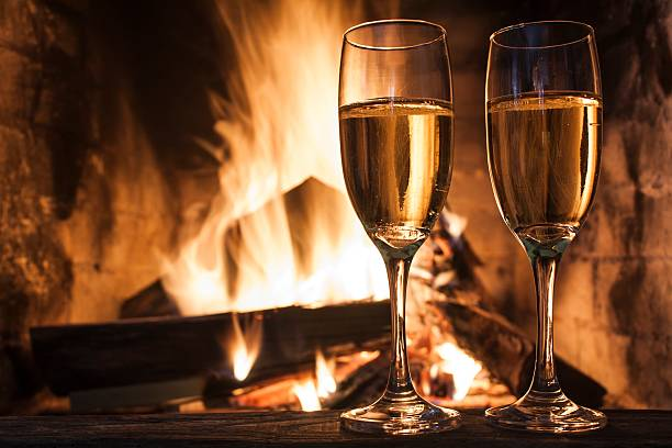 Two champagne glasses on table by a romantic fireplace stock photo