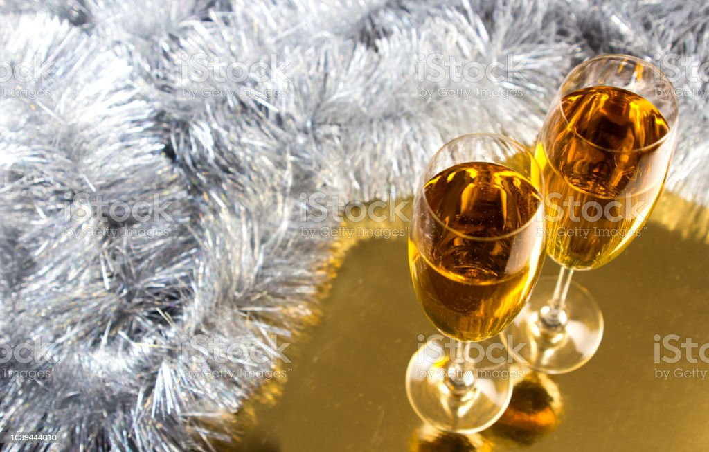Two champagne or wine glasses with gold and silver christmas tinsel...