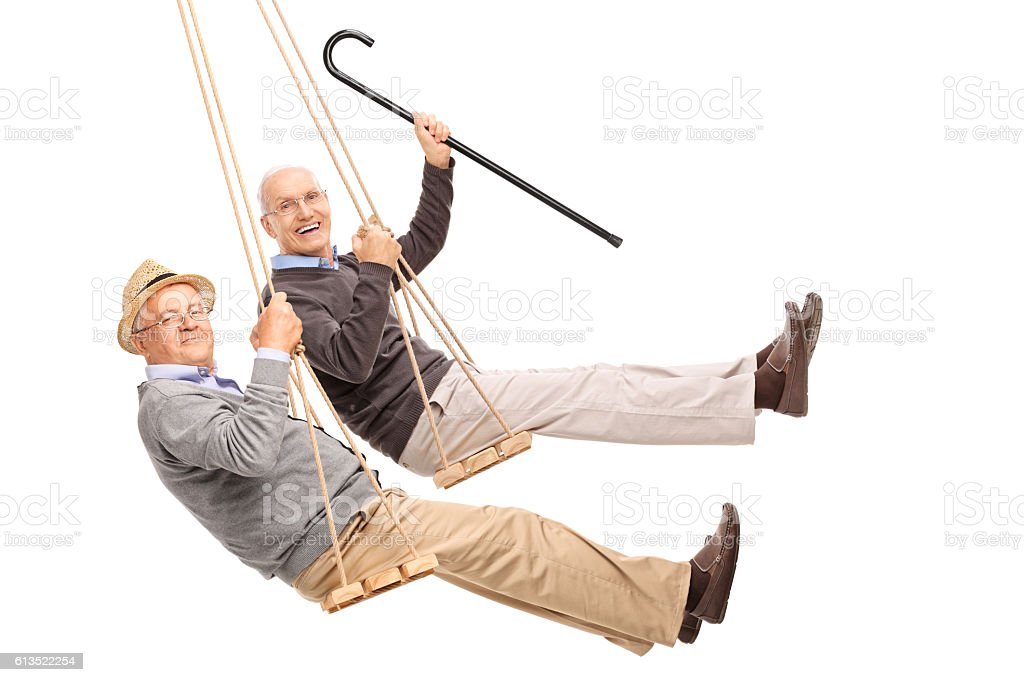 Two cheerful elderly men swinging on wooden swings stock photo