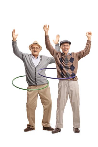 zwei fröhliche ältere männer mit hula hoops - hula hoop workout stock-fotos und bilder