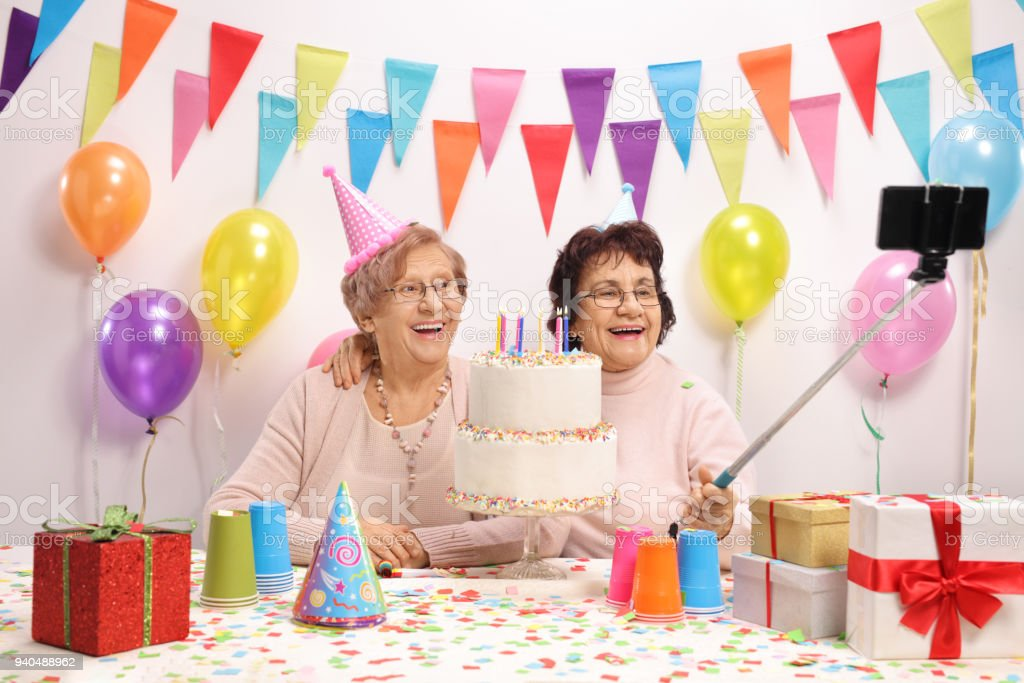 Two Cheerful Elderly Women With Party Hats And A Birthday Cake