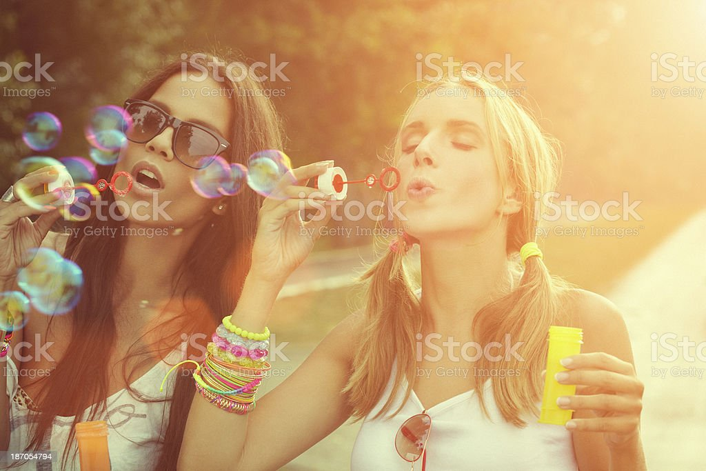 Two cheerful friends having fun and blowing bubbles royalty-free stock photo