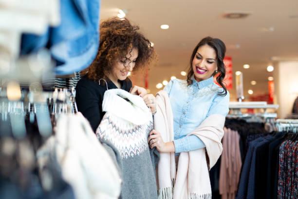 twee vrolijke meisjes winkelen voor kleding - kledingwinkel stockfoto's en -beelden