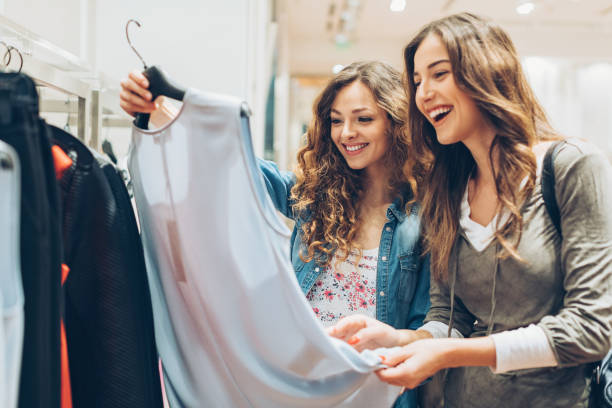 two cheerful girls shopping for clothes - shopping stock photos and pictures