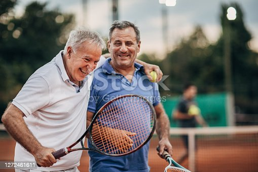 Two cheerful senior tennis players leaving tennis court after a match while smiling and hugging. Concept of healthy and fit senior people.