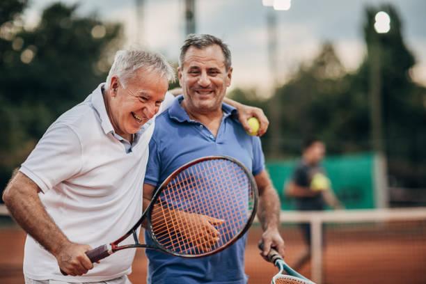 Two cheerful senior men talking while walking on the outdoor tennis court stock photo