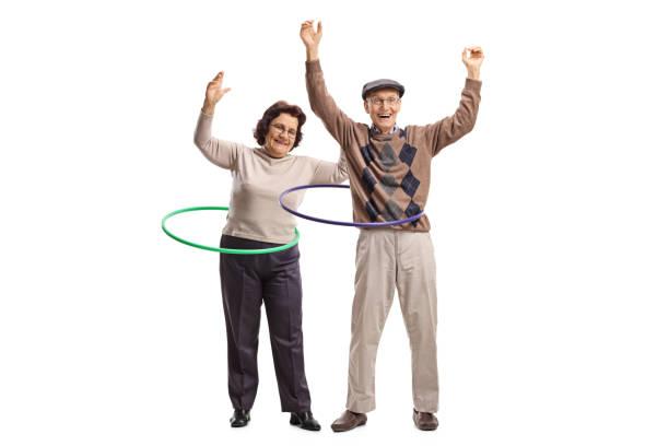 zwei fröhliche senioren mit hula-hoop-reifen - hula hoop workout stock-fotos und bilder