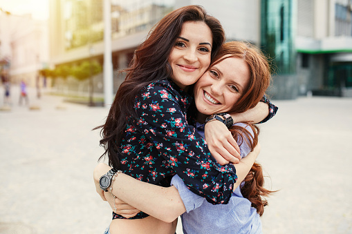 Two cheerful sisters hugging in the park