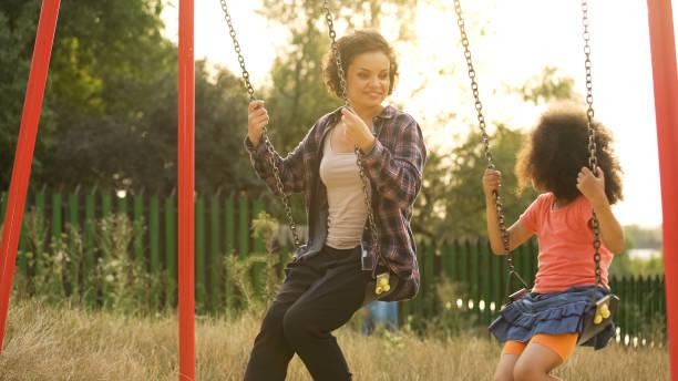 dos hermanas alegres hacer pivotar juntos en el patio de infantil al aire libre, felicidad - niñera fotografías e imágenes de stock