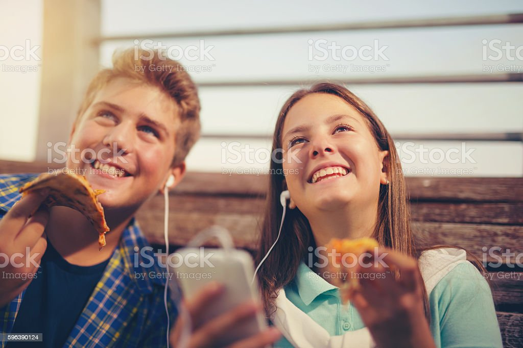 Two cheerful teenagers, girl and boy, eating pizza outdoor stock photo