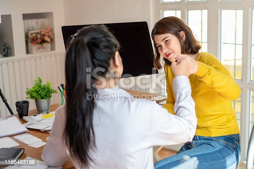 1031394114istockphoto Two cheerful woman giving high-five on the success of website design and  application on mobile. 1155463186