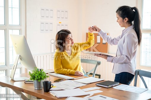 1031394114istockphoto Two cheerful woman giving high-five on the success of website design and  application on mobile. 1155465550