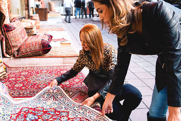 Two Cheerful Women Buying Carpets Two Cheerful women buying carpets in Istanbul. asian market stock pictures, royalty-free photos & images