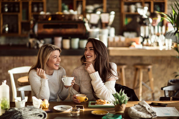 two cheerful women having fun during coffee time in a cafe. - coffee stock pictures, royalty-free photos & images