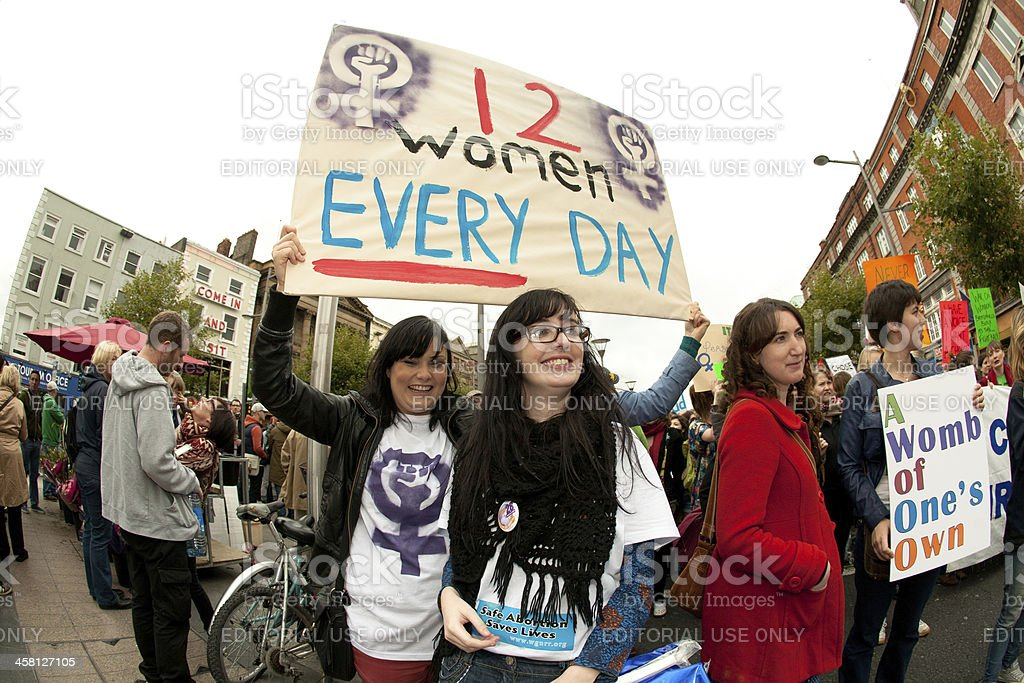 Two cheerful women holding informational poster stock photo