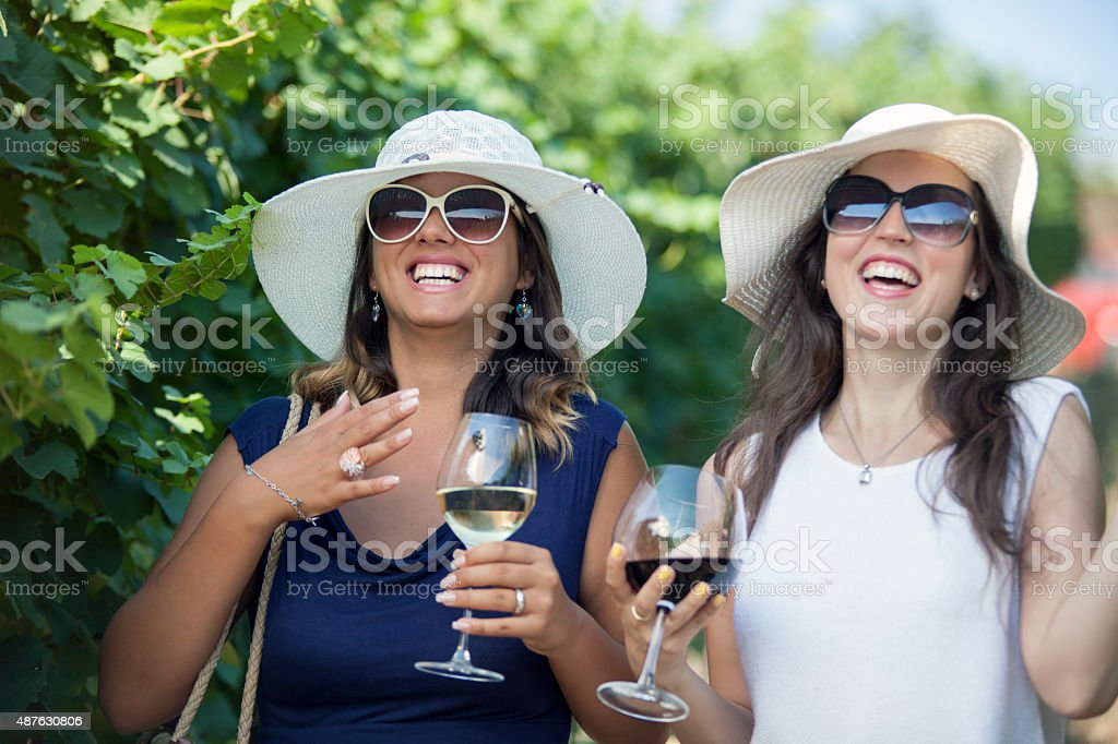 Two cheerful women laughing and drinking wine in vineyard. stock photo